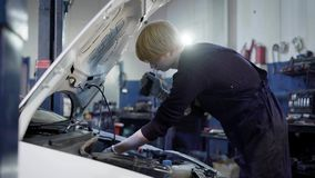 Side view of technician making maintenance of the car in garage royalty free stock photo