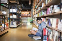 Student sitting in library by bookshelf reading. Side view of teenage boy with headphones sitting on library floor with backpack leaning on bookshelves reading Stock Images