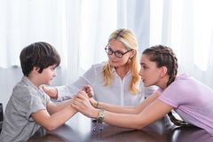 Side view of teenage girl holding hands of little brother and female counselor cheering up him. In office royalty free stock images