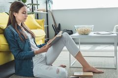 Side view of teenage girl reading book while sitting on carpet. At home royalty free stock images