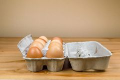Side view of ten hen eggs in a carton box on a table with copy space. stock images