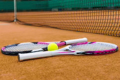 Side view on tennis rackets with a tennis ball on  clay court. Outdoors Stock Photo