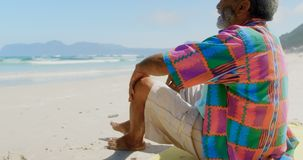 Side view of thoughtful active senior African American man relaxing on beach in the sunshine 4k stock video footage