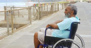 Side view of thoughtful disabled active senior African American man in wheelchair on promenade 4k stock footage