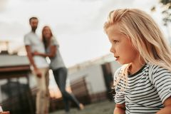 Pensive small girl relaxing opposite glad parents stock image
