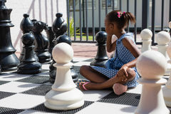Side view of thoughtful girl sitting by chess pieces Stock Images