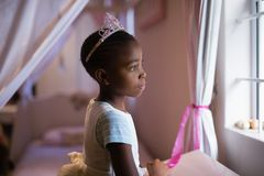 Side view of thoughtful girl wearing crown standing in bedroom. At home Stock Photo
