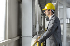 Side view of thoughtful male architect standing by railing in industry Royalty Free Stock Images