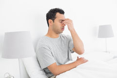 Side view of a thoughtful man sitting on bed Stock Photography