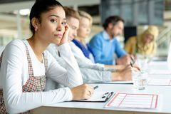 Businesswoman looking away during a business meeting in a modern office. Side view of thoughtful Mixed-race businesswoman looking away during a business meeting stock image