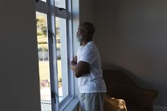 Senior man looking through window at home. Side view of a thoughtful senior African American man looking through window at home stock photo