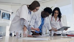 Three doctors during discussing result of analysis in the hospital. Side view of three multi ethnic doctors during discussing result of analysis in the hospital stock footage