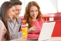 Side view of three students using laptop. Stock Photos