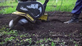 Farmer rips the ground with a cultivator. Side view of tines motorized cultivator rips ground.Farmer`s legs in black boots are buried in loose soil, preparation stock video footage