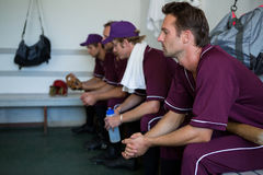 Side view of tired basball players sitting on bench. At locker room stock photography