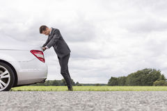 Side view of tired young businessman pushing car at countryside Stock Images