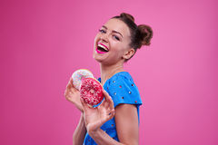 Side view of toothy laughing girl holding two doughnuts Royalty Free Stock Images