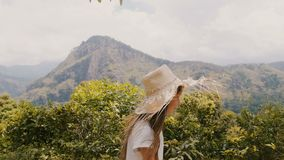 Side view tracking shot of happy little girl child in big straw hat walk along beautiful sunny forest mountain road. Carefree young female kid enjoying summer stock footage