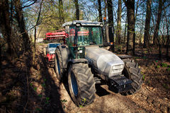 Side view of tractor on big wheels on soil road in forest Stock Image