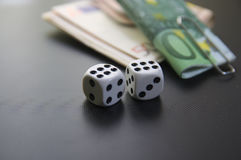 Side view of a two dices and wads of money Stock Photography