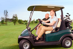 Side view of two golfer driving cart. Moving forward. Side-draw of smiling old and young golf player driving cart on course Stock Photography