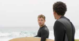 Side view of two male surfers standing with surfboard on the beach 4k stock video