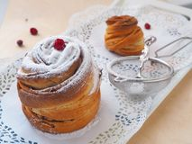 Side view of two modern desserts decorated with sugar powder. Fresh muffin or cruffin. Stock Images