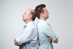 Side view of two serious men father and son standing back to back against a white background Royalty Free Stock Photos