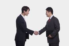 Side view of two smiling businessmen shaking hands, studio shot Royalty Free Stock Image
