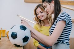 Side view of two smiling female friends watching football match at bar counter with soccer ball. And beer stock photos