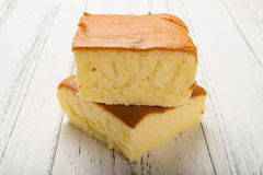 Side view two sponge cakes on white wood stock photography