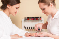 Side view of two woman sitting and smiling at spa salon. royalty free stock image