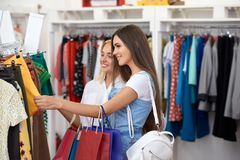 Side view of two women choosing new clothes in mall. Side view of two pretty women choosing new clothes in mall. Smiling customers looking at shirts and skirts royalty free stock photography