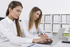 Side view of two women working Stock Images