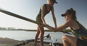 Female rowers training on a river. Side view of two young adult Caucasian female rowers preparing oars and a racing shell on a river before training stock footage