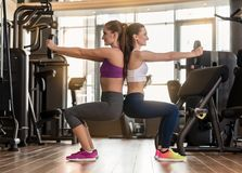 Two young women exercising together back to back with weight pla. Side view of two young women smiling while exercising together back to back with weight plates Royalty Free Stock Photo