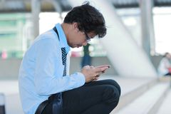 Side view of unemployed stressed young Asian man looking mobile smart phone for find job. Unemployment concept. royalty free stock photography