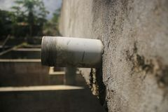 Side view of an unfinished drainage pipe sticking out a grey wall stock photography