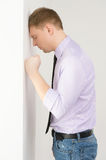 Side view of unhappy mature man. Guy resting head against wall Royalty Free Stock Image