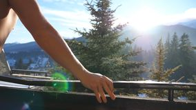 Side view of unrecognizable athletic guy standing on balcony and looking at beautiful nature on sunny day. Young man. Enjoying winter vacation or holiday stock video footage