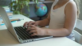 Unrecognizable little girl typing on laptop in her room. Side view of an unrecognizable little girl with long blond hair typing at her laptop keyboard sitting at stock video