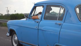 Side view of unrecognizable man in hats driving at blue retro car after rain during summer travel. Young guy moving at. His old vintage vehicle on highway. Slow stock video