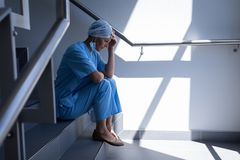 Upset female surgeon sitting on stair case in hospital. Side view of an upset Caucasian female surgeon sitting on stairs and holding her head in her hand in royalty free stock images