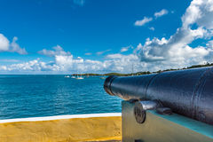 Side view of a vintage cannon facing the Caribbean ocean defendi. Ng the bay.  Blue sky with fluffy clouds.  Side view of cannon Stock Photos