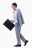 Side view of walking and smiling businessman with suitcase Royalty Free Stock Photography