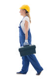 Side view of walking woman in blue builder uniform with toolbox Stock Image