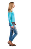 Side view of walking  woman in jeans. Royalty Free Stock Photos