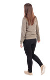 Side view of walking  woman in jeans. beautiful girl in motion. Woman with brown hair wears olive pullover and black jeans. backside view of person.  Rear view Royalty Free Stock Photo