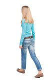 Side view of walking  woman in jeans. beautiful girl in motion. Stock Photography