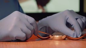 Side view of watch repairer removing back case of watch to examine watch mechanism. Time accuracy stock footage
